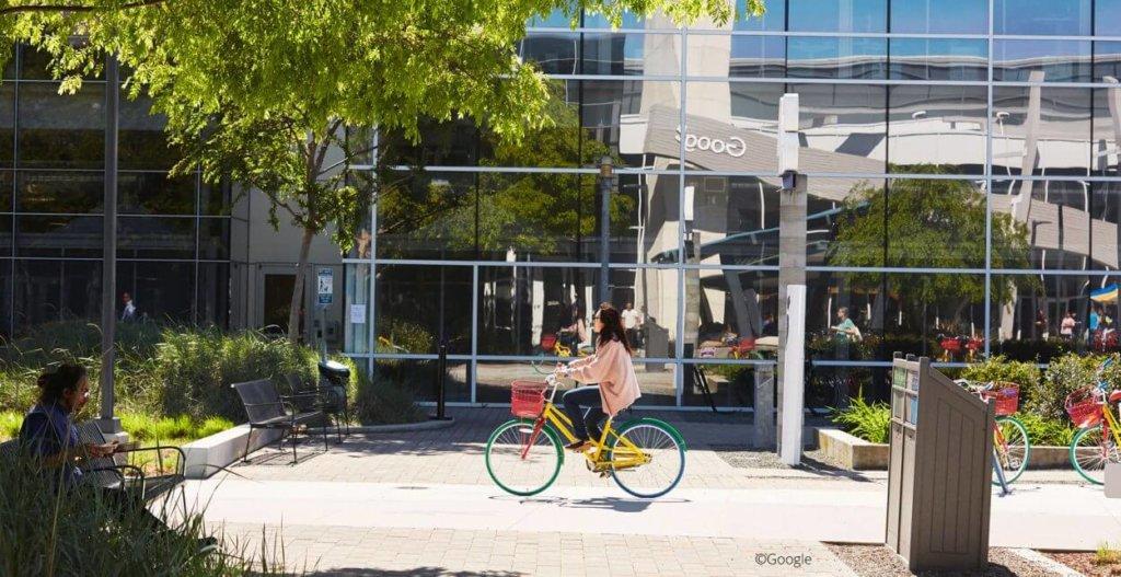 Dame som sykler på fargerik sykkel utenfor Googles hovedkvarter