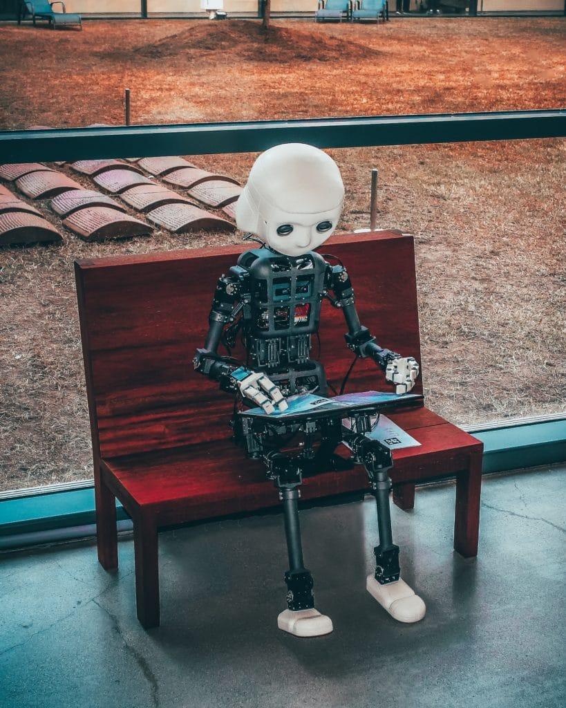 Robot sitter på en benk og lar i en bok