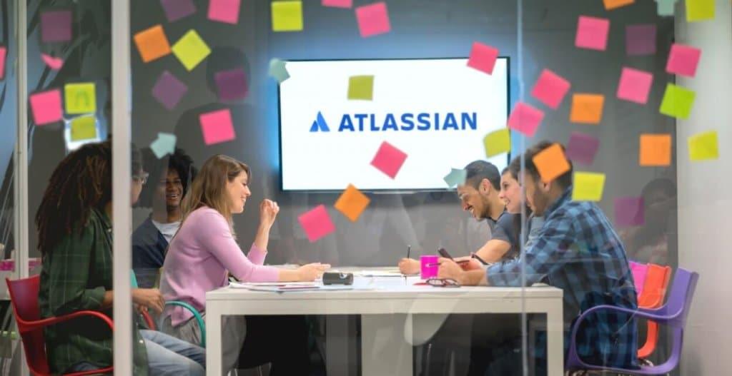 Mennesker i et møte med tv i bakgrunnen med atlassian logoen