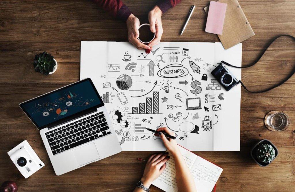 Illustrasjonsbilde med mac og forretningsplan på et bord
