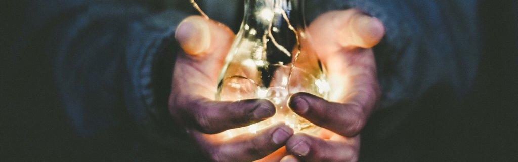 Person holder en lysende lyspære i hånden