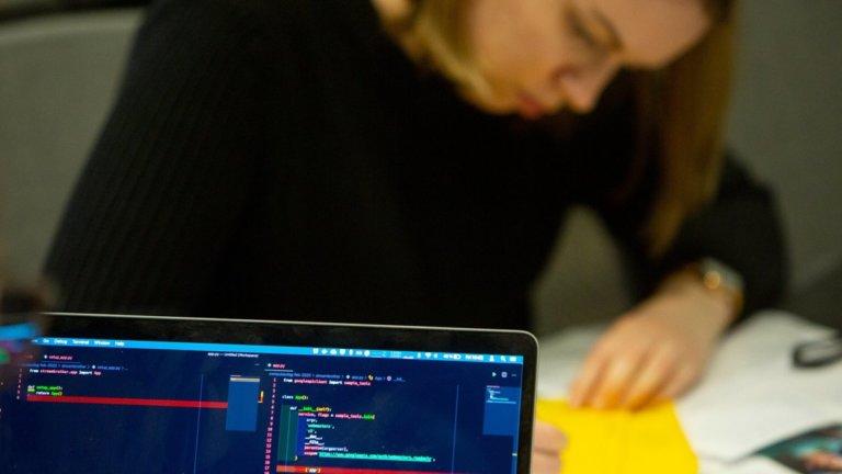 Ansatt skriver på en gul lapp under hackathon