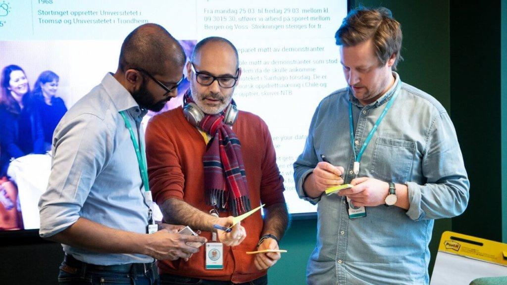 Three employees discuss during the desgin sprint