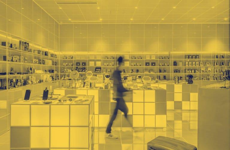 Person går gjennom en teknologi butikk sine lokaler med gul duotone