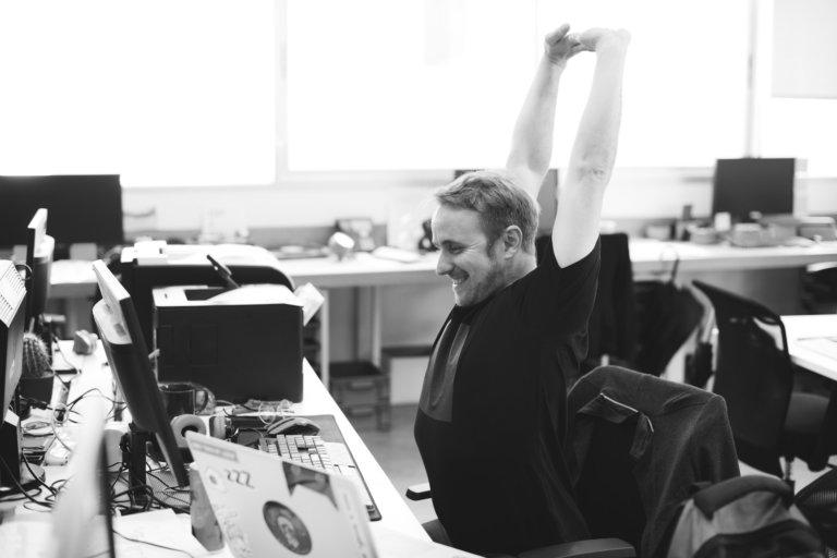 Man sits in the office and stretches his hands in the air
