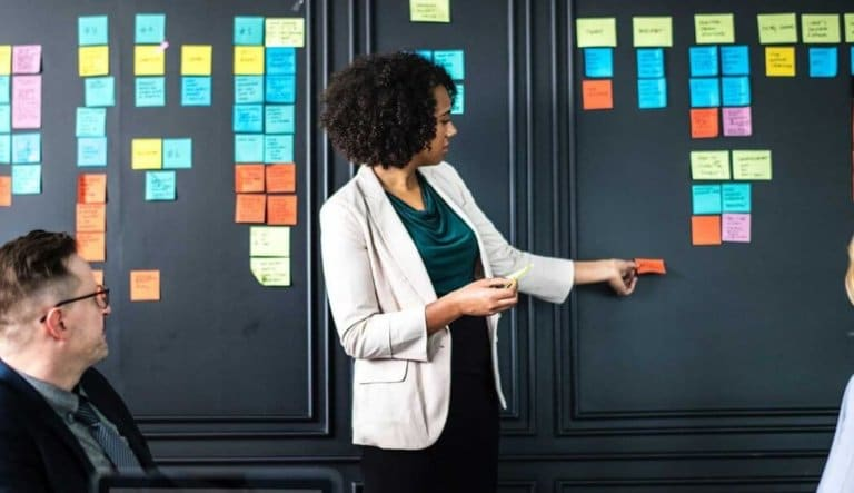 Woman placing post-it notes on a wall in meeting