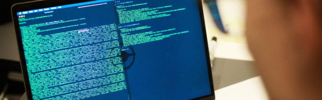 Employee codes on laptop with Computas logo