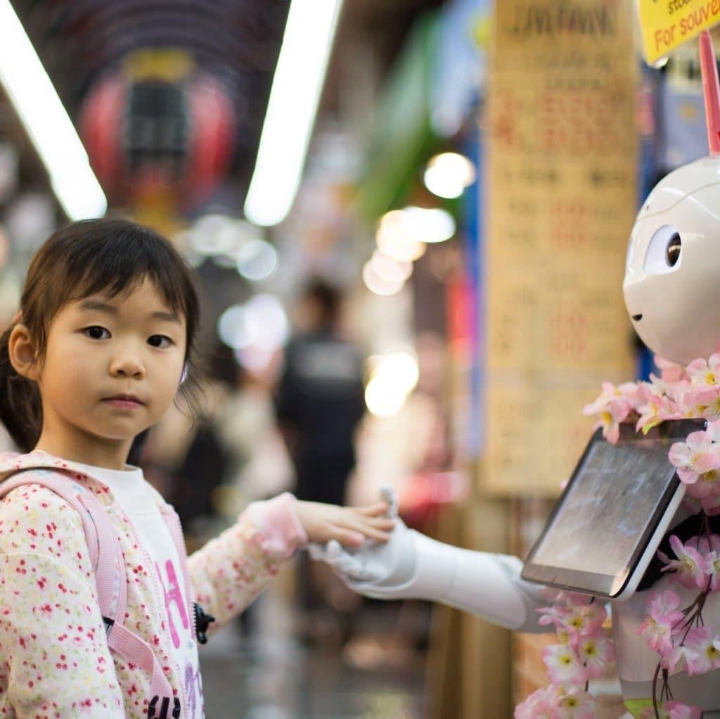 Ung jente som håndhilser med en robot