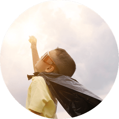 Young boy with superman cloak extends a hand in the air