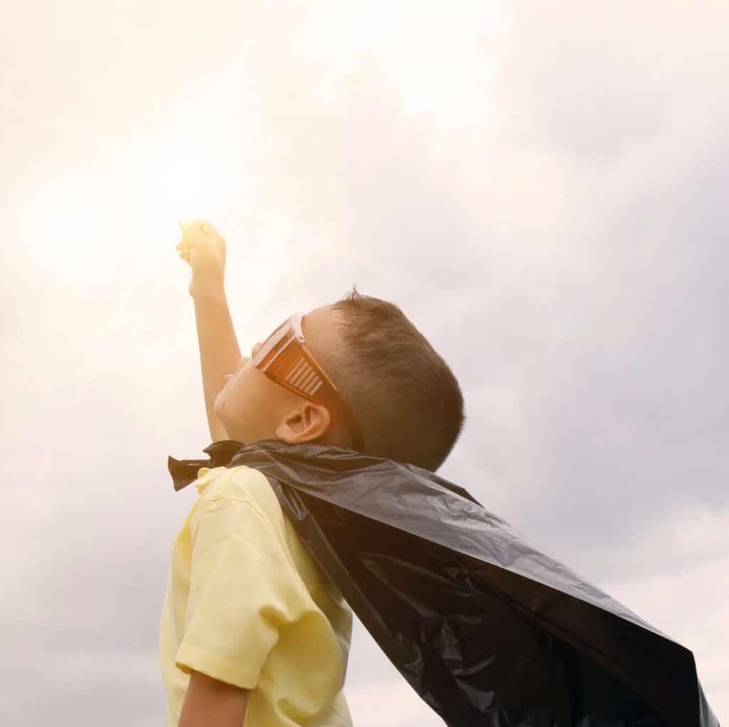 Ung gutt kledd som en superhelt strekker knyttneven i været
