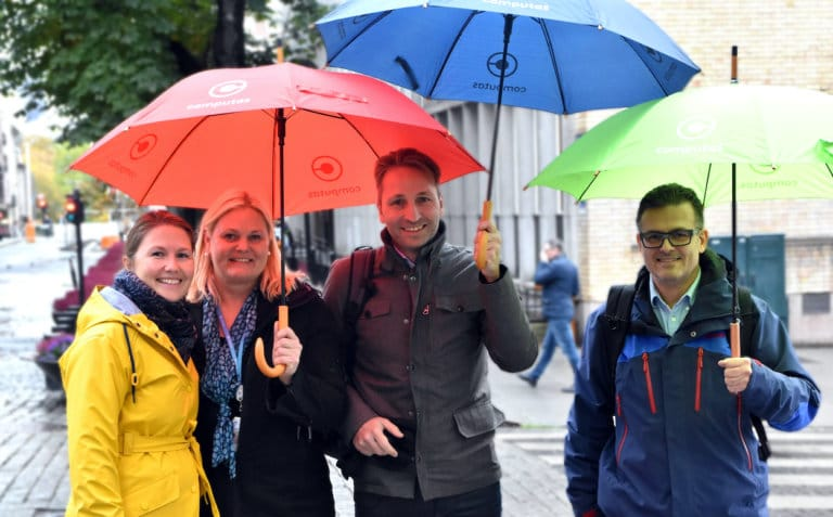 Four happy employees stand under the colorful umbrellas of Computas