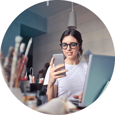 Creative woman sitting in her office looking at her phone and computer