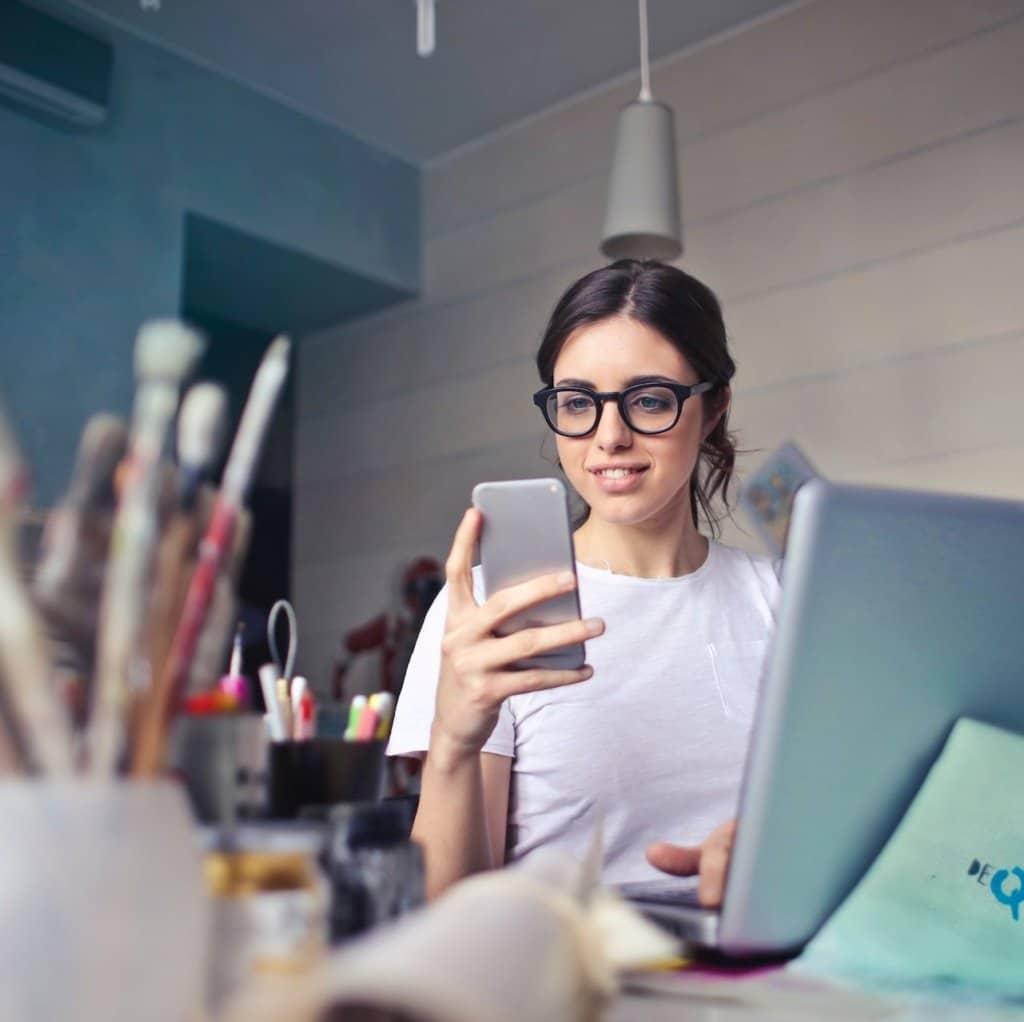 Kvinne på kontoret hennes som ser på telefonen hennes