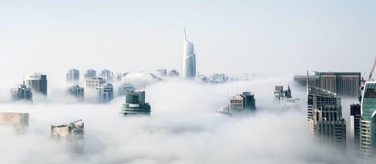Toppen av skyskrapere over skyene