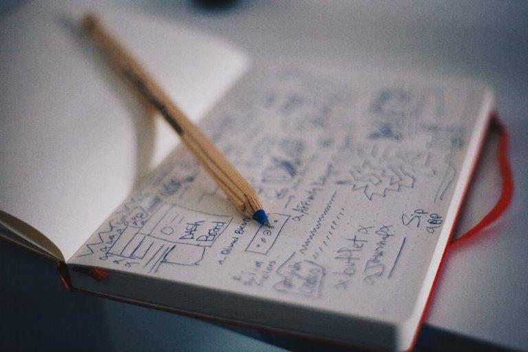 Notatbok ned tegninger og en kulepenn