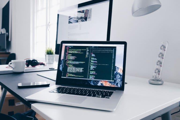 En kontorpult med skjerm, laptop og mobil