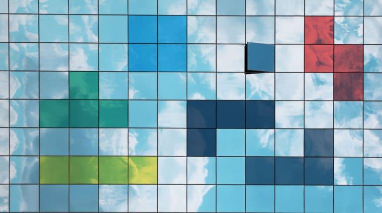 Skyer gjenspeilt i vinduer på bygning