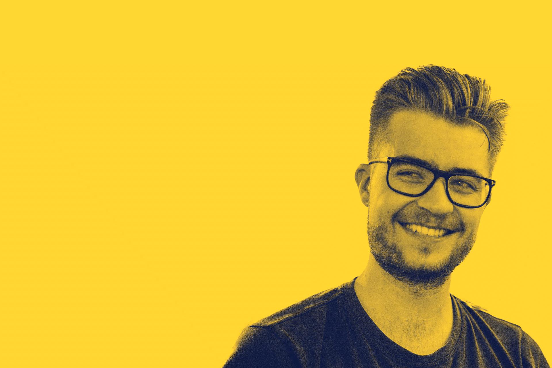 mann med briller på gul bakgrunn