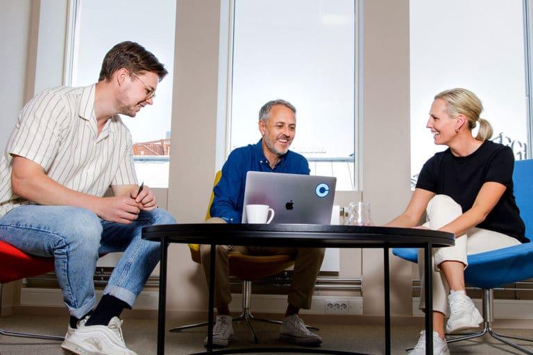 Tre computasansatte jobber sammen i avslappende omgivelser