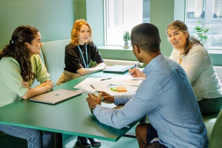 Fire mennesker jobber sammen rundt et bord