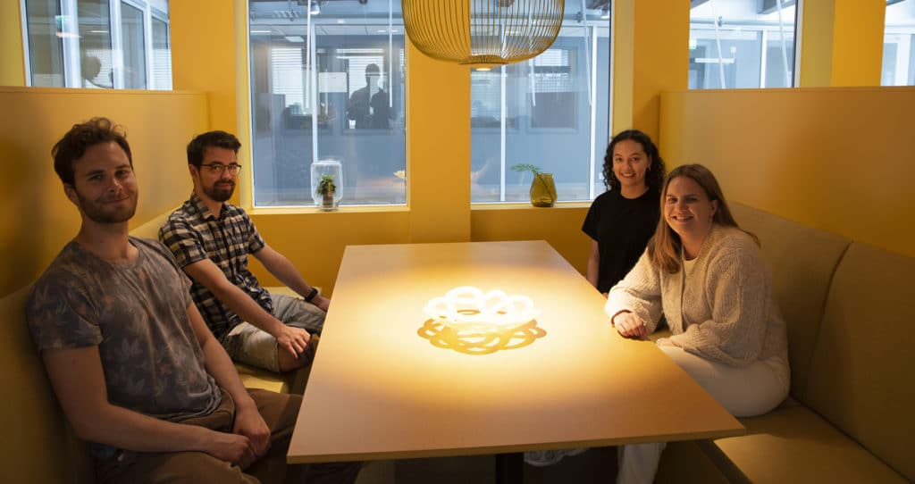 fire personer sitter rundt et bord i gult rom