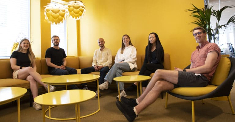 sommerstudenter i Computas sitter i en sofagruppe i et gult rom