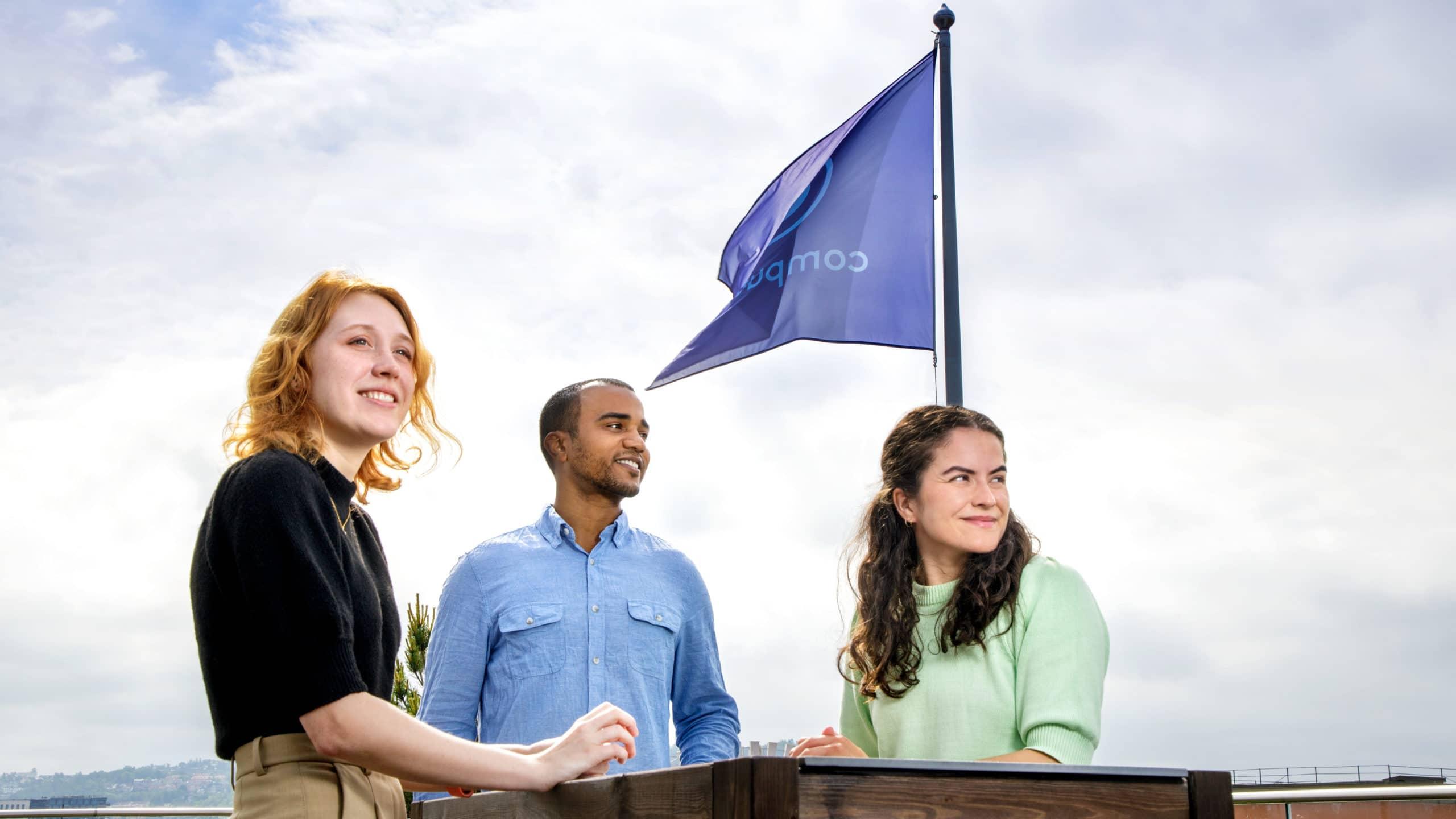 tre ansatte står på takterassen med computas-flagg i bakgrunnen